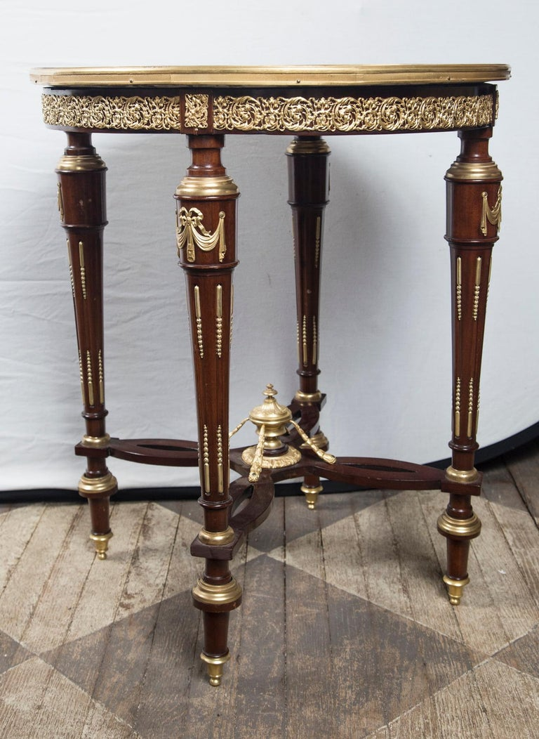 Breche violette marble top with gilt bronze mounts. The four legs attached to an unusual stretcher. topped with an urn shaped finial and four supports.