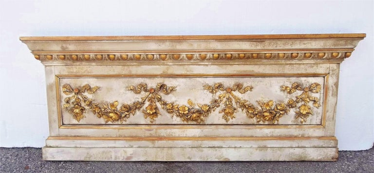 With floral festoons hung in garland form. Wear to paint and gilding as shown in photos. Centre panel (with the garlands) has a bow, more obvious from the back. Probably from a ballroom (or at least a formal room)  Gilding worn in places with red