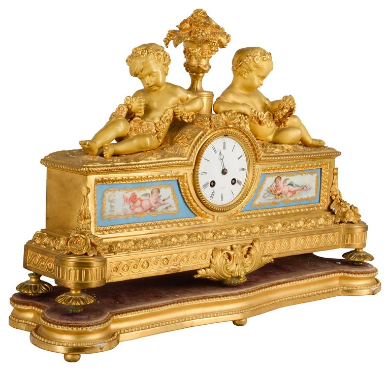 A good quality 19th century gilded ormolu Louis XVI style mantle clock, having reclining putti holding garlands of flowers either side a vase of flowers, two serves style porcelain panels depicting cherubs representing art and music. The white
