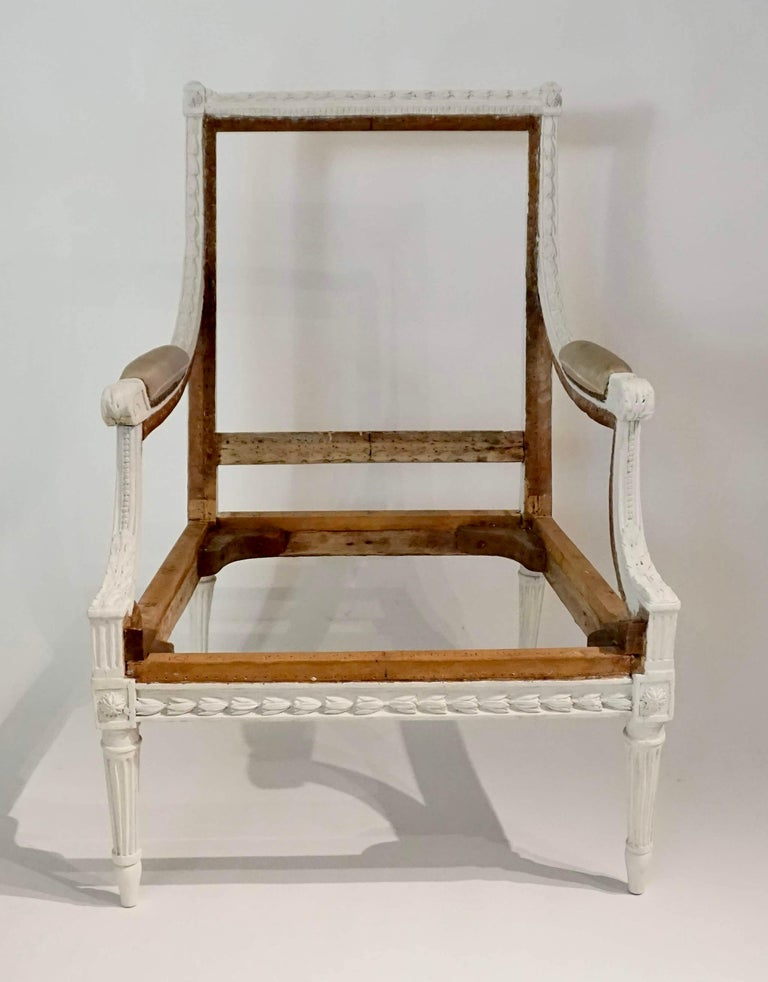 French circa 1780 Louis XVI Bergère à la Reine having painted carved wood frame with allover bellflower motifs on arms, rails, and stiles; the rectangular back issuing sloping padded arms atop sloping arm supports with bead, flute, and acanthus
