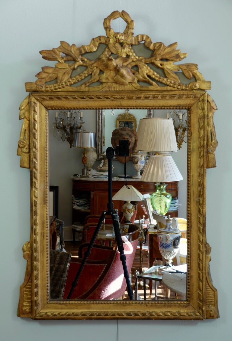 Very charming, French, Louis XVI period parcel gilt and painted marriage Trumeau mirror, featuring two birds kissing on the pediment. Other neoclassical ornaments include a laurel wreath and leaves, ribbon, swags, tassels and pearl beading. Wooden