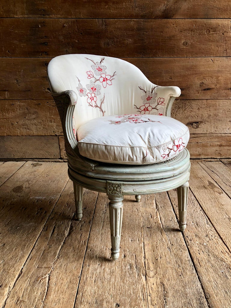 """A period Louis XVI revolving """"fauteuil de bureau"""" stamped with the name A. Gailliard (Antoine Gailliard, maitre 1781) in original grey painted finish with caned seat and back, upholstered in embroidered silk fabric."""