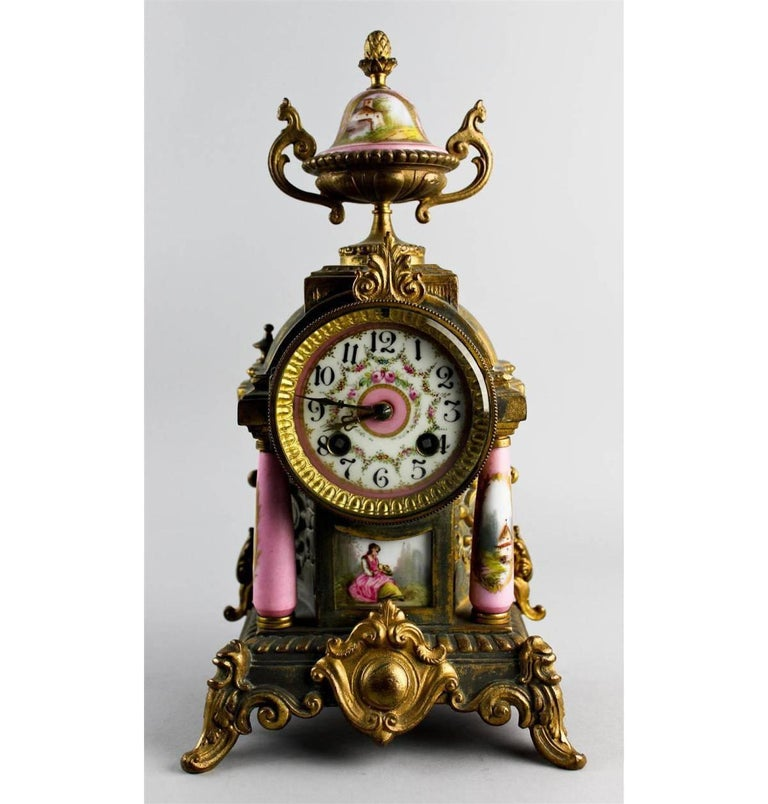 Early 20th century, the clock having a two train movement striking on a gong, with floral decorated enamel dial within an architectural housing with pink ground Sevres-style columns and urn form finial; the pair of urns, both decorated with a river