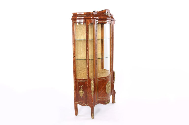 Louis XVI style with bronze mounted detail mahogany wood china display cabinet / vitrine with upholstered back interior design and glass shelves. The cabinet / vitrine is in good condition with age / use appropriate wear. The vitrine stand about 78