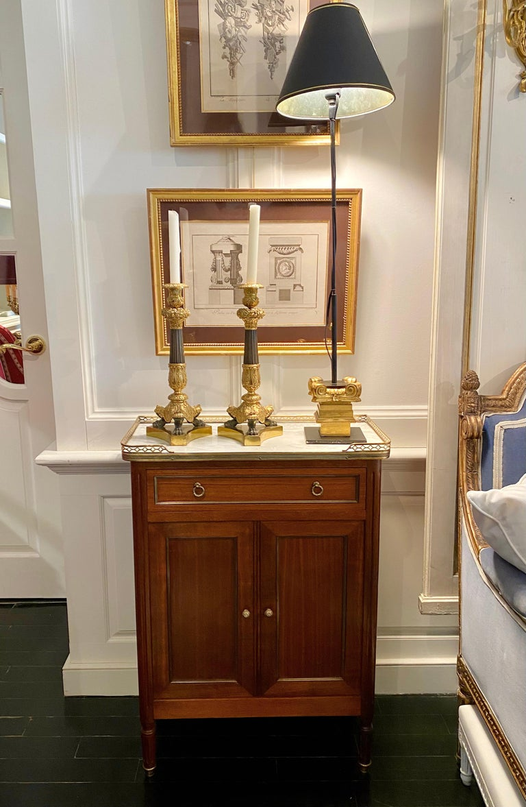 Louis XVI Style versatile cabinet or small cubboard with marble top and bronze gallery. Rectangular white marble top with rounded corners surrounded by a bronze pierced gallery. The cabinet has a drawer above a pair of doors opening unto shelves. It