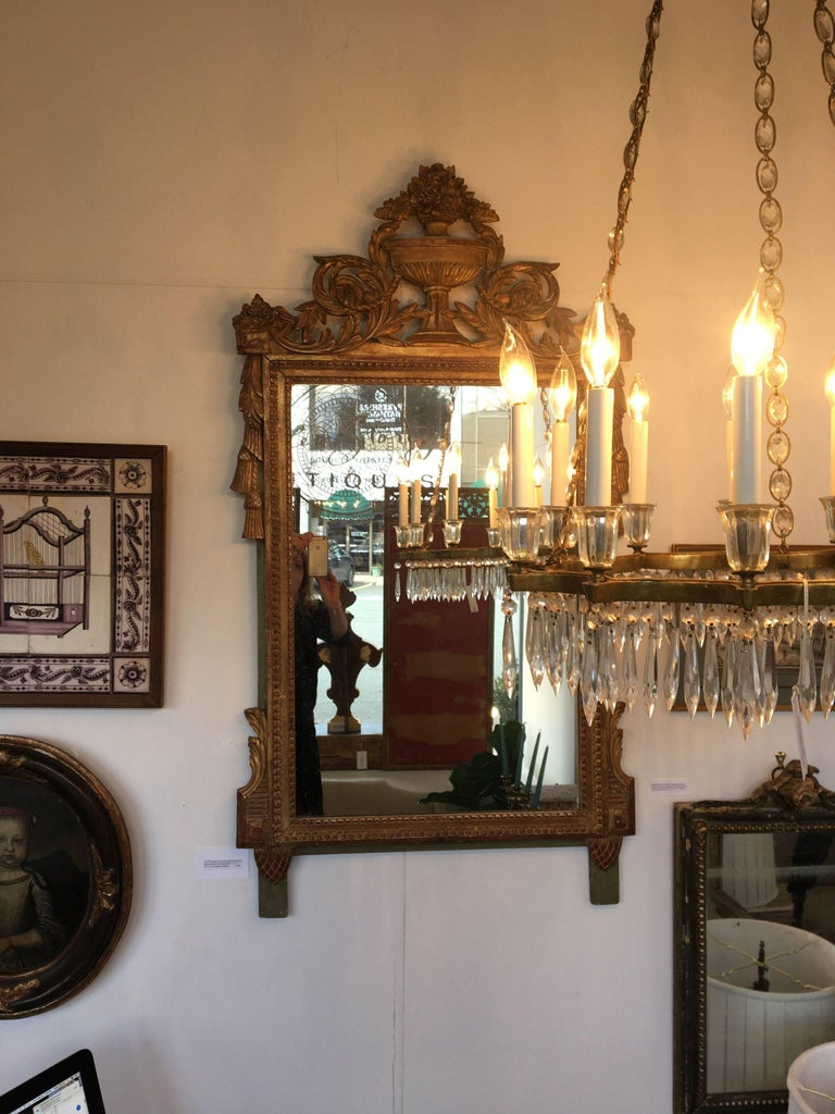 """A 19th century Louis XVI style carved and gilded French Provincial mirror, 50"""" H. x 20"""" W. In excellent condition."""