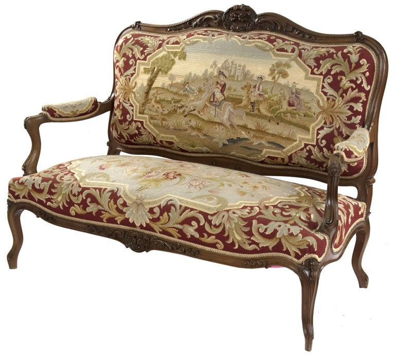 A Louis XV-style carved walnut sofa with gros point needlepoint upholstery in the style of Aubusson tapestry. The carved and shaped upholstered backrest, which depicts a hunting scene: men on horseback follow hunting dogs that are cashing a stag