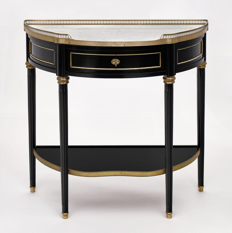 """Console, French, """"demilune"""" in the Louis XVI style featuring an intact Carrara marble top and opened brass gallery. There is gilt brass trim throughout. We liked the single drawer in the apron of this elegant piece. The wood has been ebonized and"""