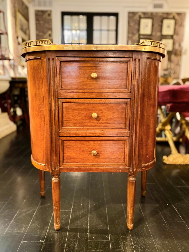Louis XVI Style cabinet or commode chest of drawers with marble top and bronze gallery.  Demi-lune white marble top with rounded corners surrounded by a bronze pierced gallery. The cabinet is fronted by three drawers. It is mounted on four Louis