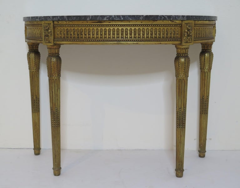 A Louis XVI style demilune console table with grey and white marble top. Ball and tooth finished apron with flower blocks. Leaf designed capitals above tapered and fluted legs. Excellently carved and decorated.