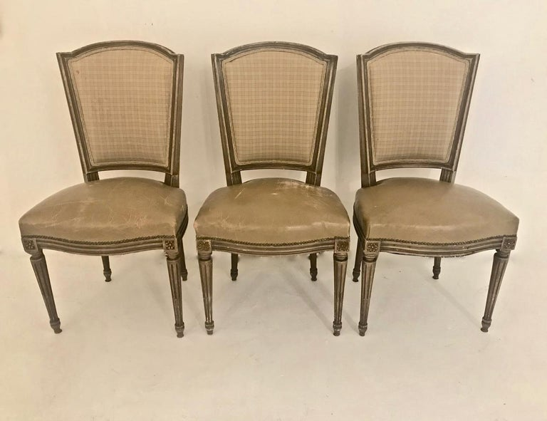 This is a highly decorative set of 6 French Louis XVI-style dining chairs that date to the first half of the twentieth century. The chairs retain their vintage caramel-colored French fabric backs that coordinate perfectly with the beautifully