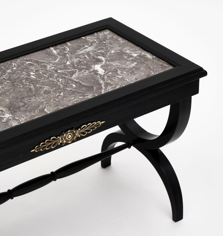 Louis XVI style ebonized coffee table from France made of walnut that has been ebonized and finished with a French polish. The finely cast bronze accents add a lovely detail and there is one dovetailed drawer. We love the inserted Sainte Anne gray