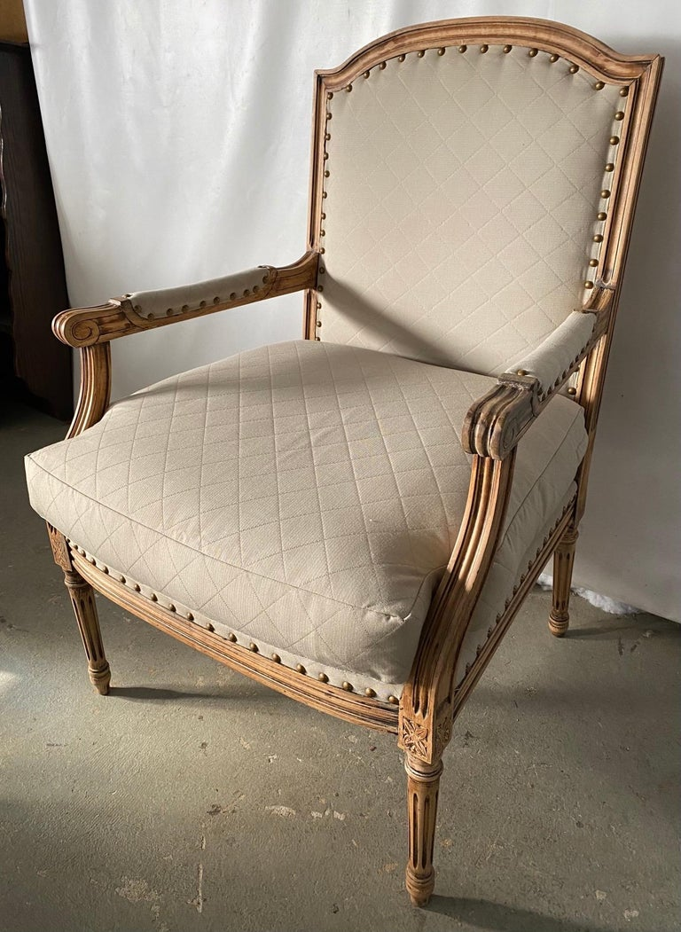 Elegant French Louis XVI style armchair with complementary side chair in bleached wood frames, fluted leg and cubic blocks decorated with florets, upholstered in classic beige quilted fabric. Appropriate for dining, desk or vanity chair in a modern,