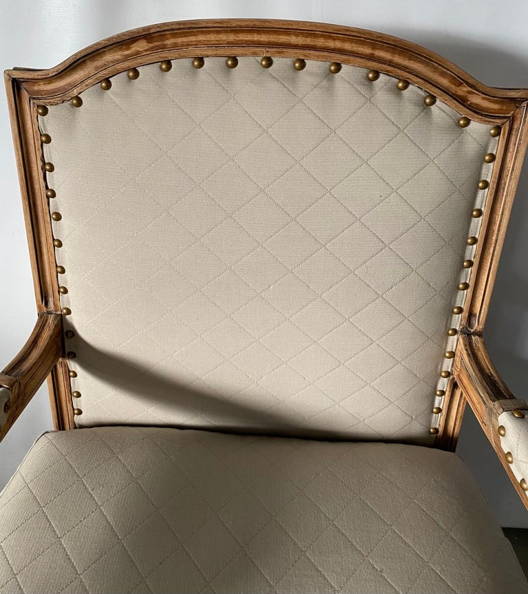Elegant French Louis XVI style armchair with bleached wood frame, fluted leg and cubic blocks decorated with florets, upholstered in Classic beige suited fabric. Appropriate for dining or desk chairs, vanity chair in modern or traditional French,