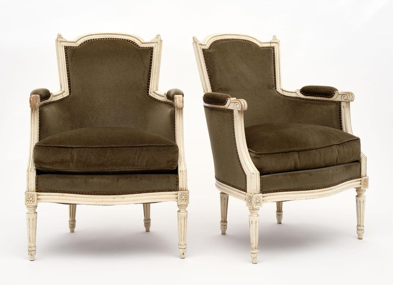Louis XVI style French antique bergères with hand-painted beech wood frames and original velvet upholstery in good condition. They are quite sturdy and add a beautiful, Classic element to any space. We love the green hue of the fabric as well.