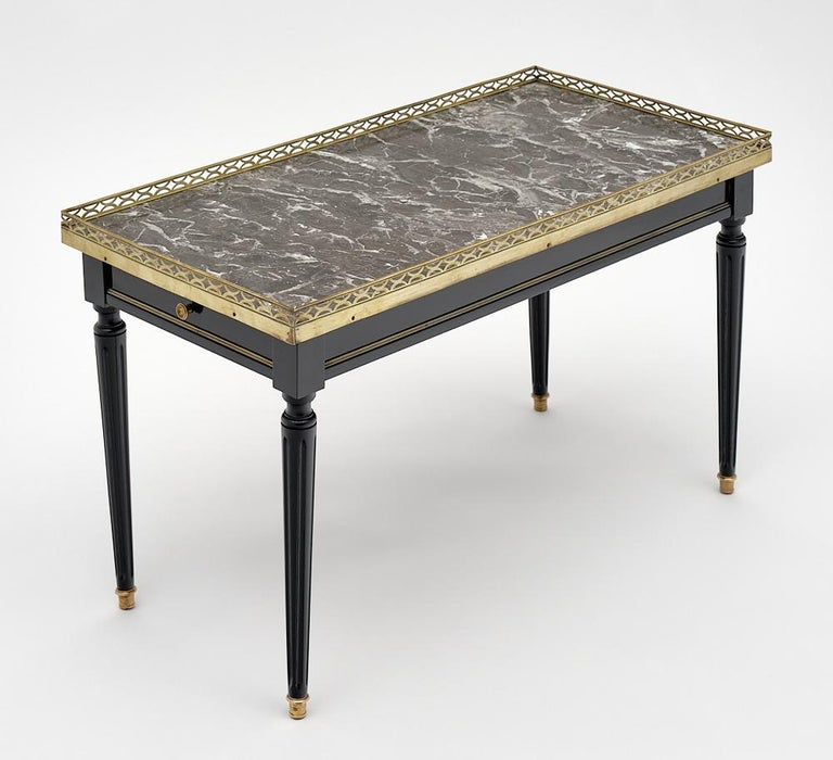 Louis XVI style French coffee table made of solid mahogany that has been finished in a lustrous ebonized French polish. We love the gilt brass trim throughout and the Classic lines of this piece. It is topped by an original; intact Sainte Anne