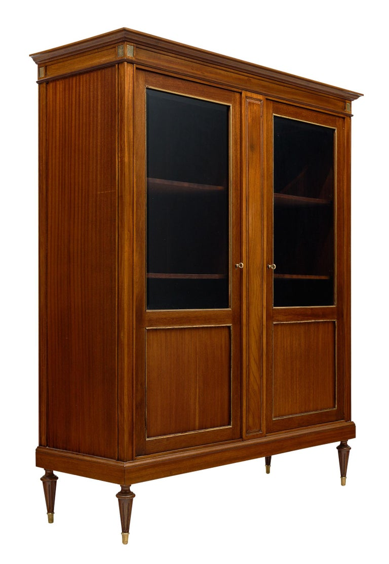 Louis XVI style French mahogany bookcase with wonderful brass trim throughout and interior shelving to house your priceless collectables or book collection. We love the warmth of the mahogany and the strong; Classic details and proportions.