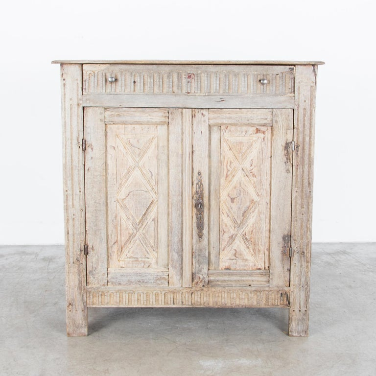 An oak buffet from France, circa 1860, featuring two doors which open onto an interior shelf. The simple silhouette is embellished by provincial carvings in pretty, geometric patterns, including a harlequin motif on the door panels, and an elaborate