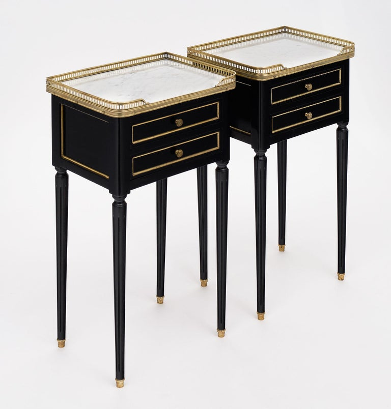 Pair of side tables, French, in the Louis XVI style with intact Carrara marble tops and opened gilt brass galleries. Each features two dovetailed drawers and fluted, tapered legs. The gilt brass trim throughout contrasts beautifully with the