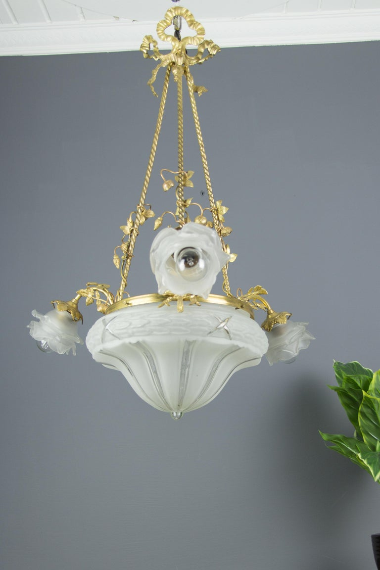 French Louis XVI style gilt bronze and frosted glass four-light chandelier, embellished with bronze flowers, has three arms, each with frosted glass floral shape lampshade and original E27 socket with new wiring. Measures: Height is 28.3 inches /