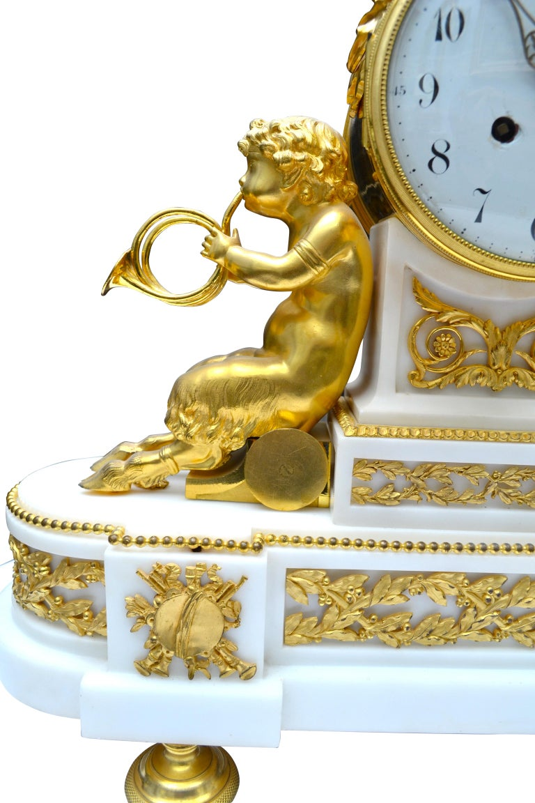 Louis XVI style clock with Bacchante and musical satyrs. The body of the clock features two young satyrs in gilded bronze each holding twin horns; they lean back against the shaped white marble clock plinth supporting the white enamel dial. Atop the