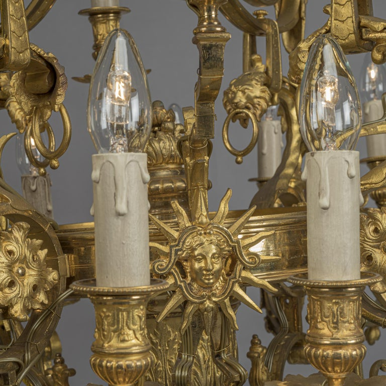 A fine Louis XVI style gilt-bronze twenty-four-light chandelier, cast with chimera and masks of Apollo.