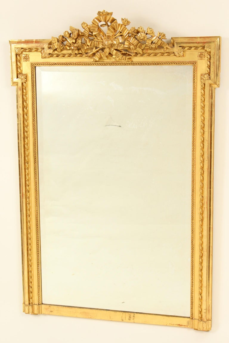 Louis XVI style giltwood mirror, circa 1930-1950. This mirror has excellent gold leaf gilding and beveled glass. The pediment is gesso and gold leaf.