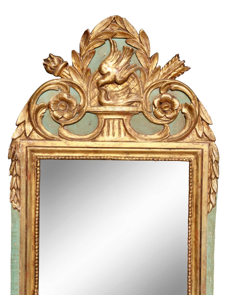 With laurel leaf with central bird crest over a mirror set in a conforming frame.