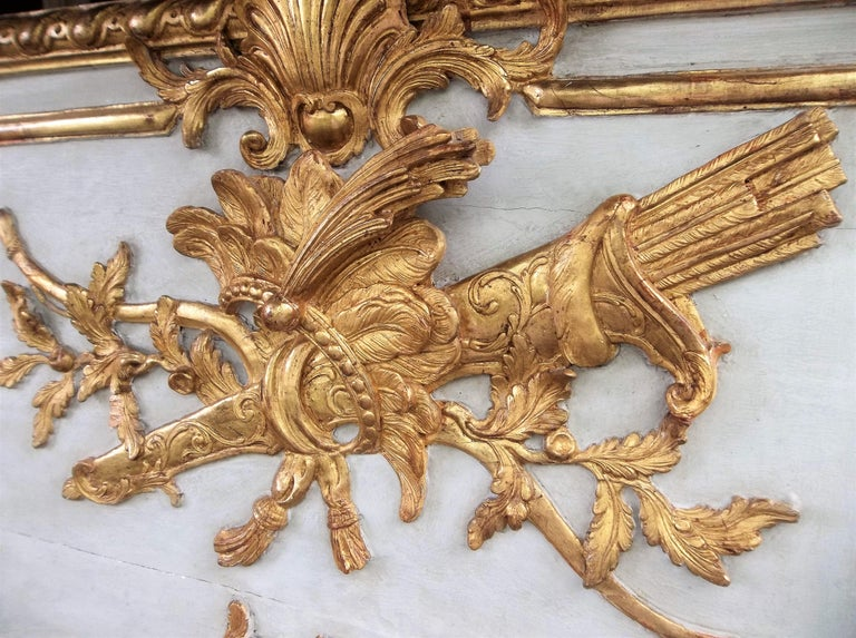 French Louis XVI trumeau mirror with raised gilt bow and quiver with feathered headdress in relief. Water gilt and matte gilding throughout.  Most likely cut from a room of boiseries (niches on back indicate paneling attachment) the crème paint with