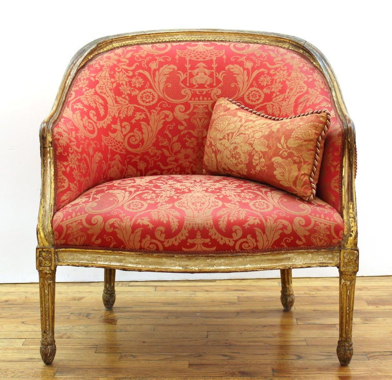 French Louis XVI style fauteuil with carved giltwood frame and damask upholstery, with small cushion.