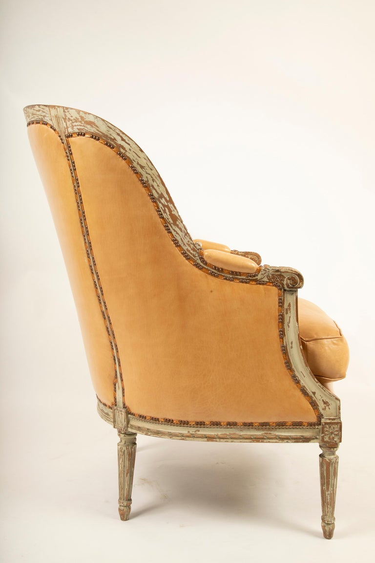 An exceptionally large grey painted Louis XVI style bergère. Upholstered in very high quality leather with parcel gilt leather tape and stop/group decorative tacking, circa late 19th century four available, priced individually.
