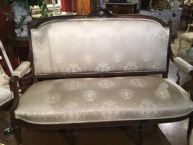 Beautiful five piece living room suite, Louis XVI style made in walnut with A carved wreath of roses at the crest of the sofa and all of the chairs. All are newly upholstered in white silk damask fabric. Reed and tapered Legs. All pieces are