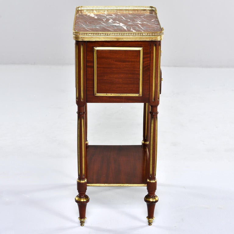 Louis XVI mahogany side cabinet has a marble top with brass gallery and two functional drawers with brass pulls, circa 1850s. Sides have brass trim, reeded legs have gilded details and turned feet.  Marble top has cracked corner - see detail photo.