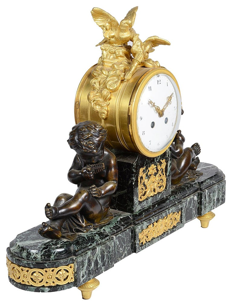 A good quality late 19th century French Louis XVI style mantel clock, having a pair of bronze putti either side of the eight day duration, chiming clock, mounted by a pair of gilded ormolu Doves, raised on a green marble base and ormolu feet.