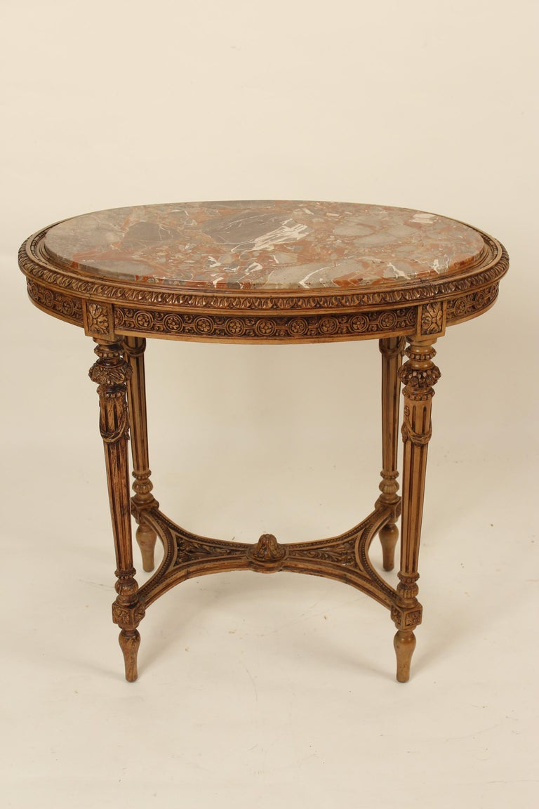 Louis XVI style carved oval beechwood occasional table with marble top, circa 1930. Exquisite carving on this table.