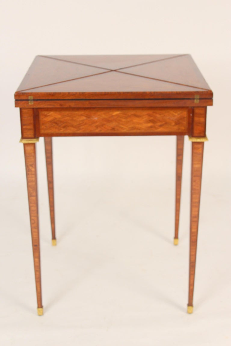 Louis XVI style tulip wood and mahogany napkin fold games table with gilt bronze mounts and a tooled leather playing surface., signed (stamped) Haentges, Paris, circa 1920. Dimensions when napkin folds are closed, height 30.5