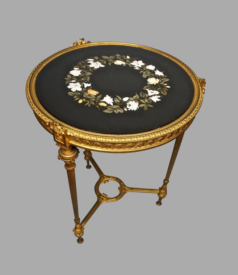 A good quality Louis XVI style gilt bronze side table inset with an Italian Pietra Dura circular top decorated with flowers on a dark ground, circa 1880.