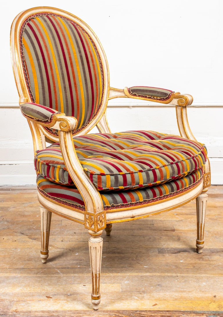 "Pair of Louis XVI style fauteuils, the frames parcel gilt and cream painted around the oval backs and cushioned seats with striped velvet upholstery, the scrolling arms with rosette block details above fluted tapered legs. Measures: 35"" H x 25"" W x"