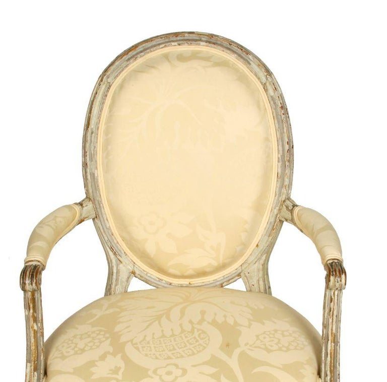 Louis XVI style painted fauteuil with oval back and pale yellow damask fabric.