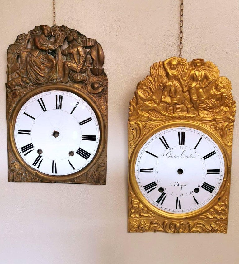 These two particular pediments were originally parts of antique pendulum clocks; the central circular portion is in white fire enamel with fine Roman numerals in black and is set on an embossed and gilded brass plate; on the gilded and burnished one