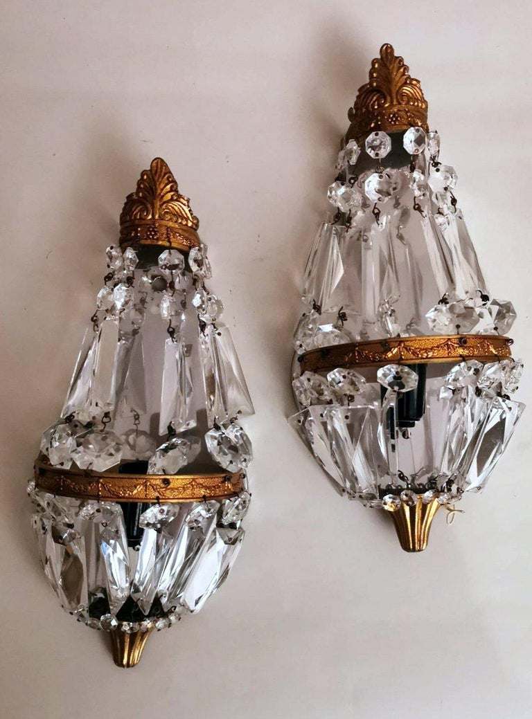 Small and graceful pair of wall sconces with the typical balloon shape; the brass structure is enriched by refined decorations depicting soft garlands; the entire frame of each sconce is adorned with lead crystals, cut, ground, and faceted, joined