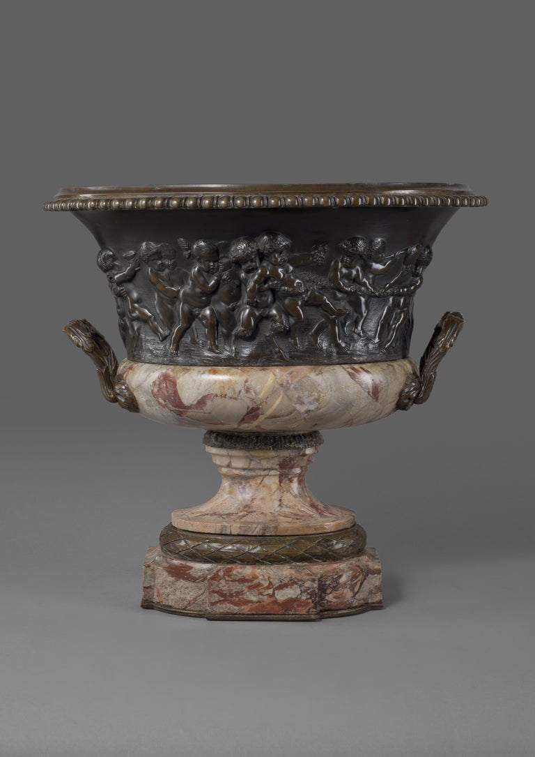 A Louis XVI style patinated bronze and marble jardinière, cast in relief with Bacchanalian Scenes Of Putti at Play, After Clodion.  French, circa 1870.   The body of the jardinière or vase depicts a charming scene of putti at play in the manner