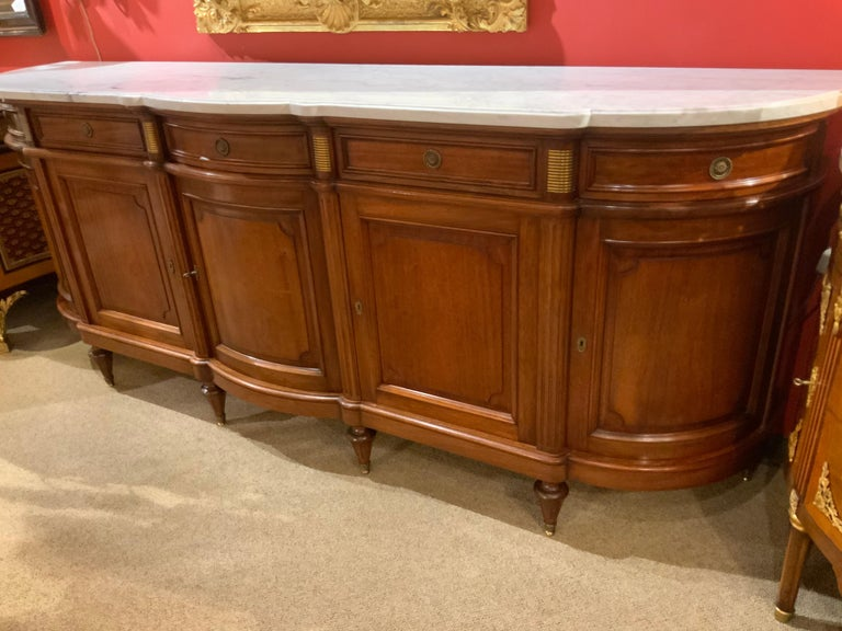 Excellent quality sideboard made of mahogany with a white marble top over a conforming case. This piece has five doors with five drawers above. It rises on Louis XVI style leg with sabots. The piece is beautifully curved in the center and on the