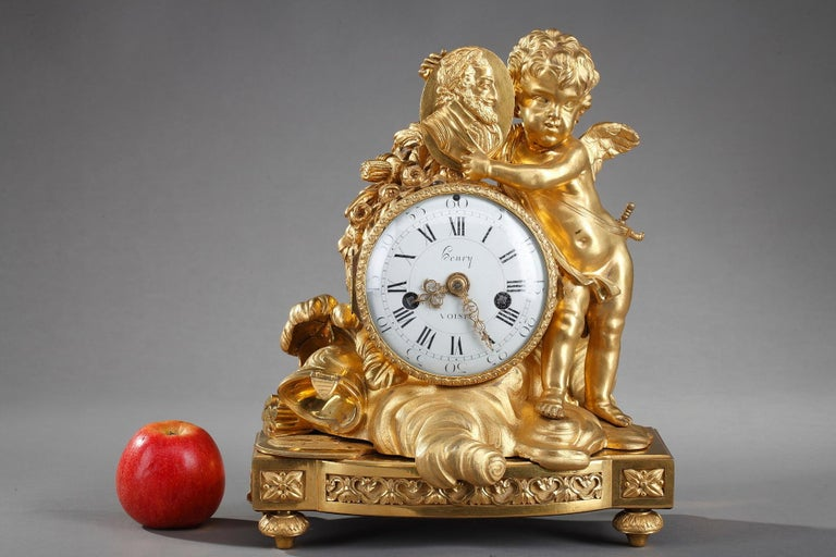 Late 18th century Louis XVI table clock crafted in gilt bronze featuring a winged Cupid presenting a medallion portrait of the founder of the Bourbon dynasty in France, the king Henri IV (1553-1610). Cupid carries the sword, symbol of the king's
