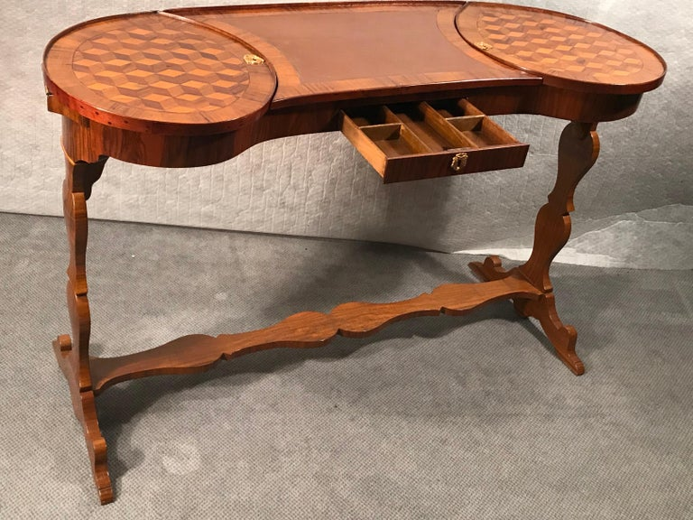 Exquisite and very unusual kidney shaped working table, France 1780, walnut, maple, plum wood veneer and marquetry. With a leather top and a flap on each side. One central drawer. Beautiful piece in very good original condition.