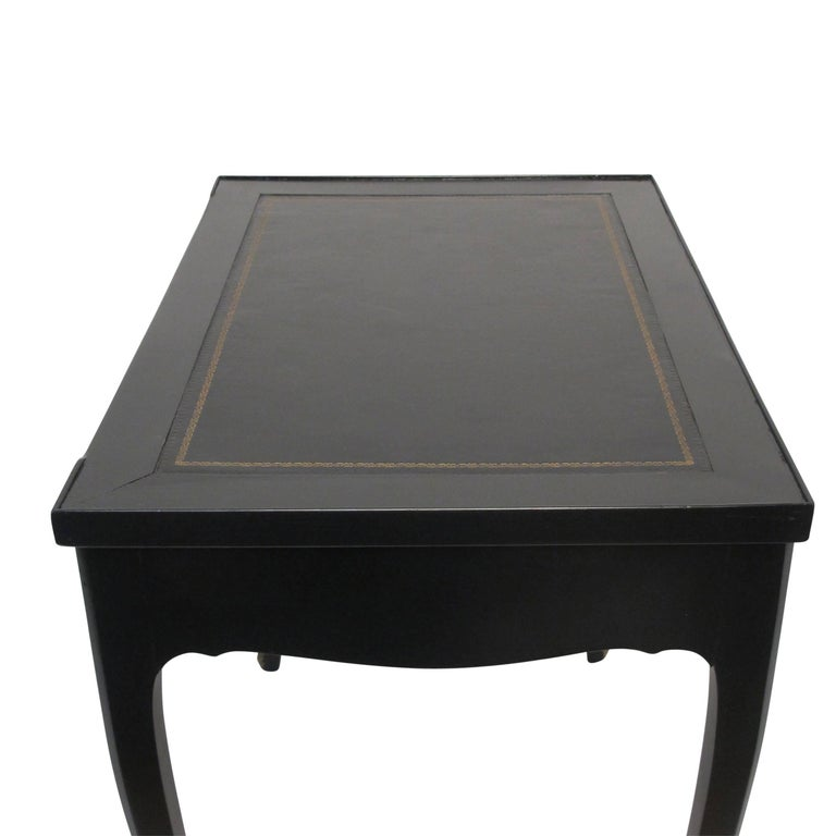 Stylish black lacquered writing table and tric trac games table. The writing surface having inset leather with gold tooling. The interior of the games table inlaid with green and yellow backgammon board, the reverse of the top laid with green baize