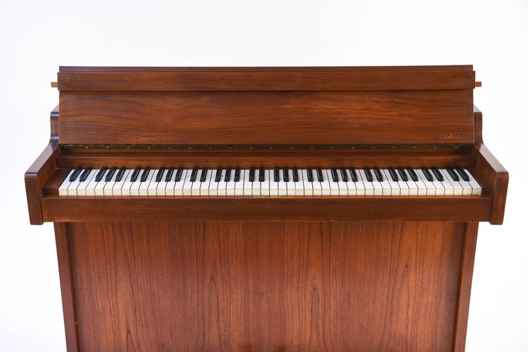 This modernist Danish pianette, termed pianette due to the 82 keys rather than the standard 88 of a full size piano, is made of figured teak, by renowned piano maker Louis Zwicki. This piece would be perfect for an apartment due to its compact size.