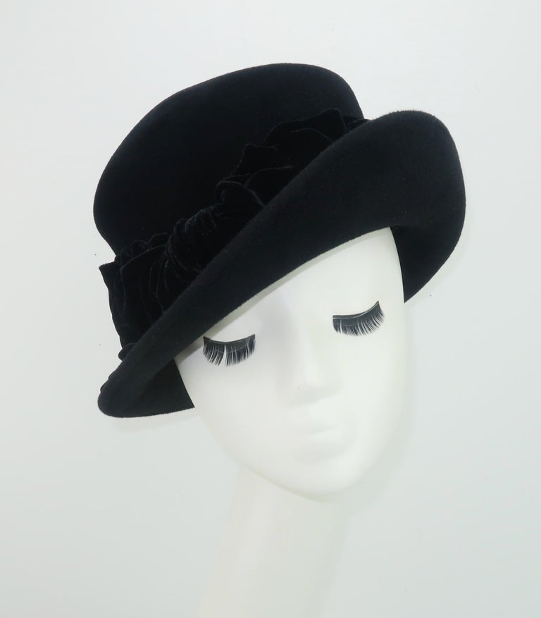 A vintage inspired black wool felt hat with upturned brim and crushed velvet bow by British born and Los Angeles based milliner, Louise Green.  From the beginnings of her millinery business in 1987 until her recent retirement, Ms. Green has been