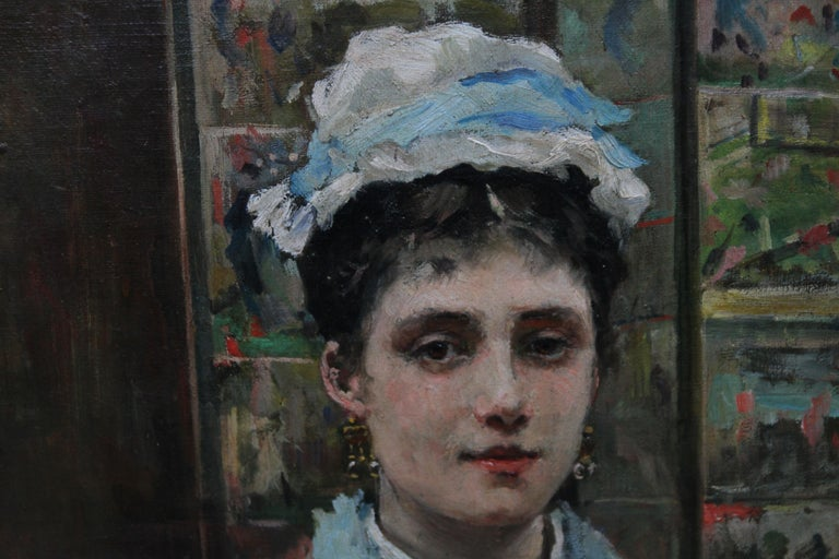 This superb oil on canvas painting is by British Victorian female artist Louise Jopling. Painted in 1875 the painting is a three quarter length self portrait of the artist painting herself from a reflection. She is seated wearing a light blue gown