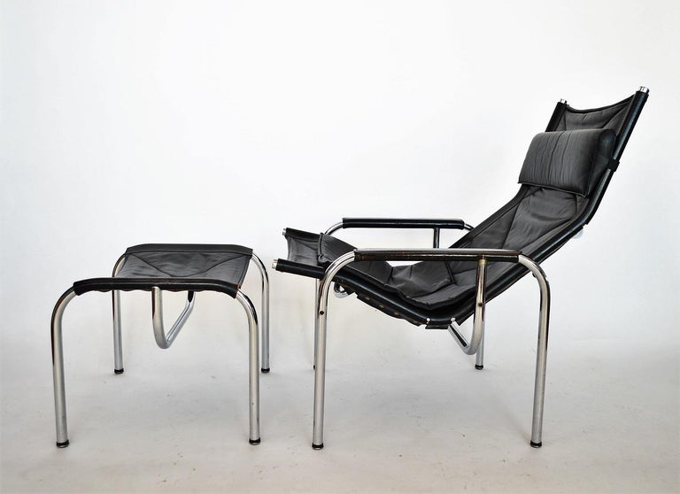 Complete set of black lounge chair with ottoman, headrest and leather cushion designed from Hans Eichenberger for Swiss company Strässle. Designed and produced during the 1970s. Good vintage condition with signs of wear and age on the leather.